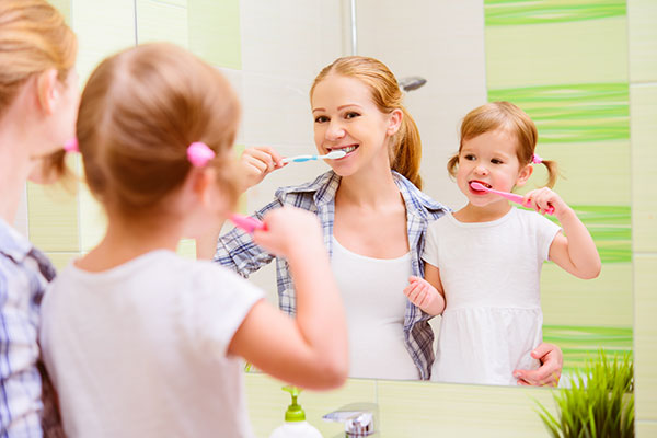 A woman teaching her kid brushing to brush her teeth in Rockville Centre, NY.